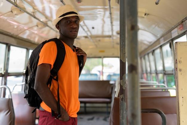 Młody turysta mężczyzna stojący podczas jazdy autobusem w bangkoku w tajlandii