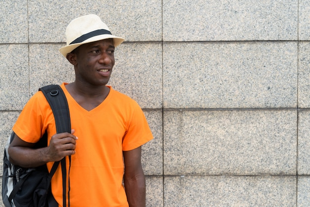 Młody turysta mężczyzna trzyma plecak, myśląc i patrząc na odległość na ścianie z bloku betonowego