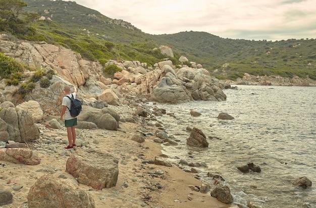 Młody turysta odwiedza klif typowy dla południowej sardynii podczas zachodu słońca