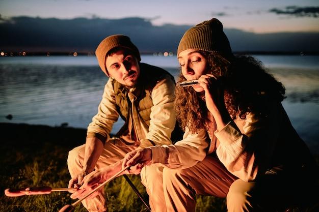 Młody turysta patrząc na swoją żonę grającą na harmonijce przed ogniskiem, jednocześnie smażąc kiełbaski na tle jeziora lub rzeki
