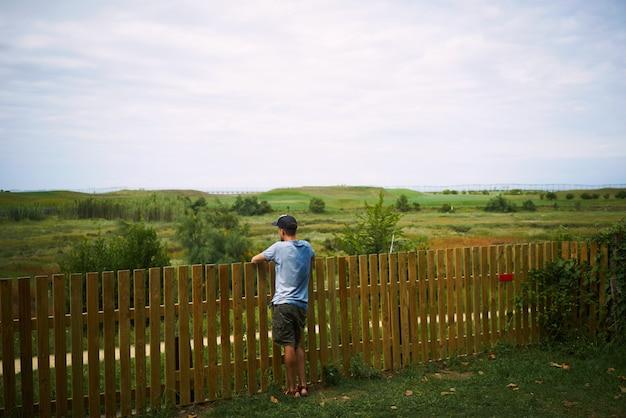 Młody turysta patrząc na zielony krajobraz stojący ogrodzeniem