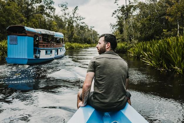 Młody turysta pływający drewnianą łódką po pięknej rzece w dżungli borneo w kalimantanie. wycieczka, aby zobaczyć dziką przyrodę wyspy. fotografia podróżnicza.