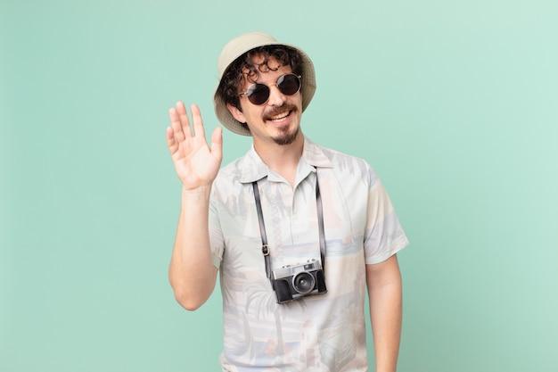 Młody turysta podróżnik uśmiechnięty radośnie, machający ręką, witający i witający