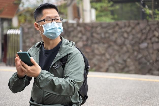 Młody turysta podróżuje sam i używa smartfona, aby znaleźć sposób z noszeniem maski, okularów