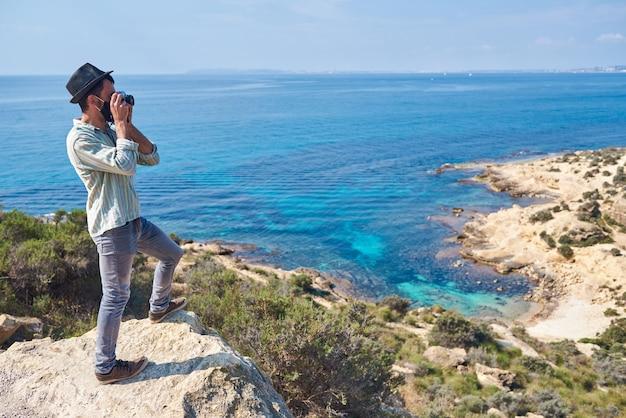 Młody turysta robi zdjęcie ze szczytu wzgórza, na którym widać morze o pięknych kolorach