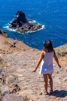 Młody turysta spacerujący ścieżką klifową przy zejściu na czarną plażę bujaren, na północ od wyspy la palma na wyspach kanaryjskich. hiszpania