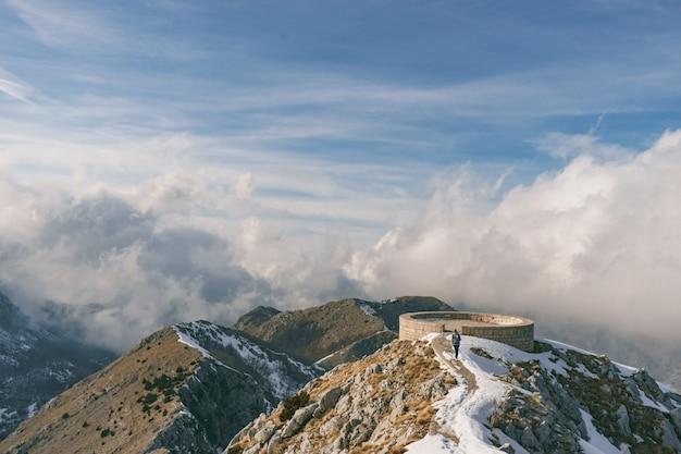 Młody turysta stoi w pięknych górach na wycieczce pieszej