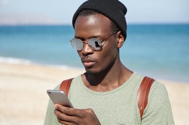 Młody turysta ubrany w stylowe nosić wpisując wiadomość tekstową na telefon komórkowy
