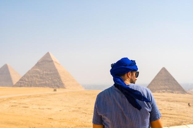 Młody turysta w niebieskim turbanie i okularach przeciwsłonecznych podziwiający piramidy w gizie, kair, egipt
