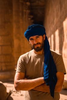 Młody turysta w niebieskim turbanie odwiedzający rano świątynię edfu w pobliżu miasta asuan. egipt