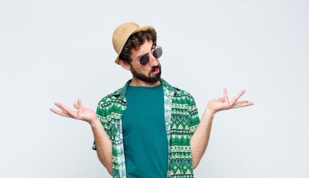 Młody turysta wzrusza ramionami z głupim, szalonym, zdezorientowanym, zdziwionym wyrazem twarzy, czuje się zirytowany i nieświadomy białej ściany