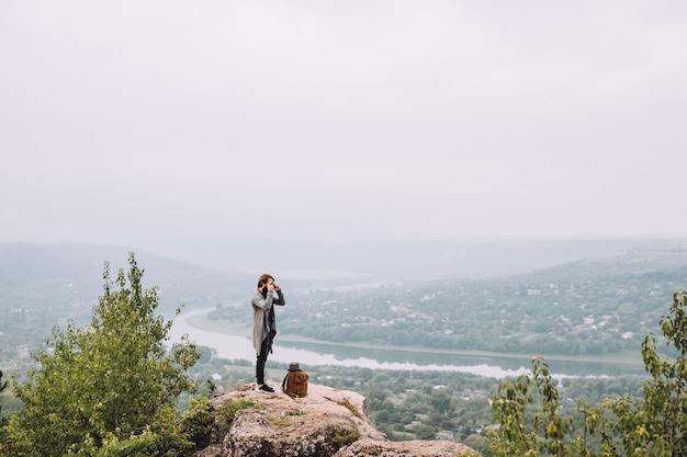 Młody turysta z brodą na szczycie góry.