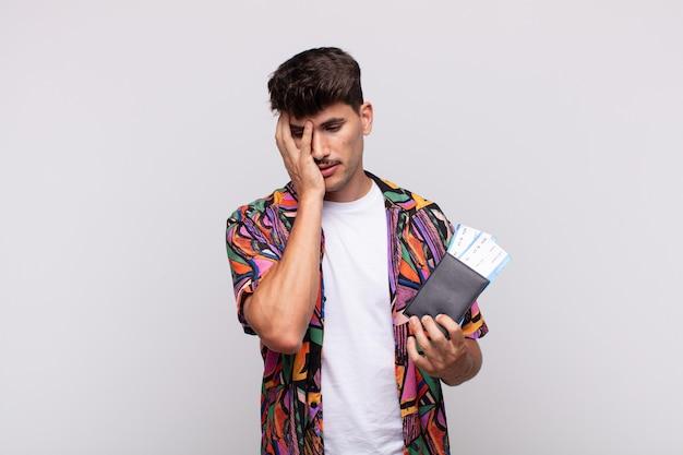 Młody turysta z paszportem czuje się znudzony, sfrustrowany i senny po męczącym, nudnym i żmudnym zadaniu, trzymając twarz dłonią