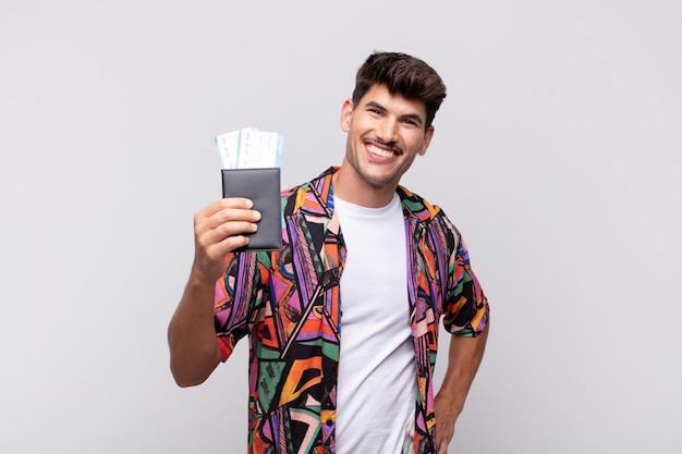 Młody turysta z paszportem, uśmiechnięty radośnie, z ręką na biodrze i pewną siebie, pozytywną, dumną i przyjazną postawą