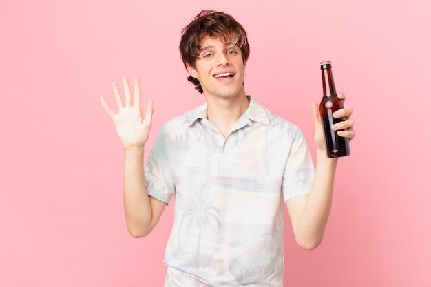 Młody turysta z piwem uśmiechnięty radośnie macha ręką witając i witając