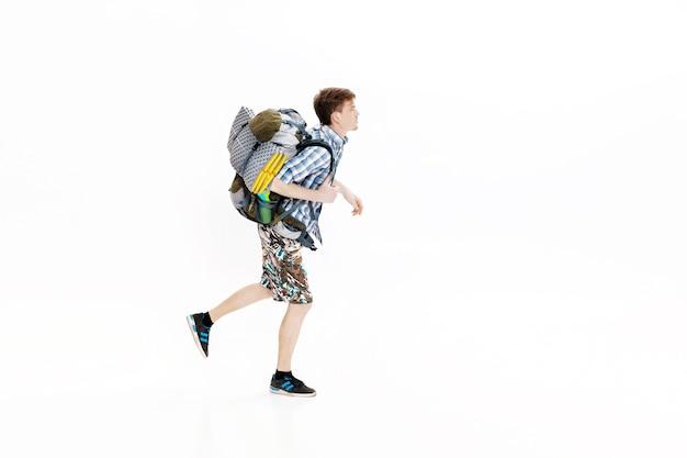Młody turysta z plecakiem biegnącym na białym tle turysta się spóźnił