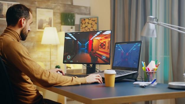 Młody twórca gier testujący interfejs strzelanki. twórca gry pracuje w nocy.