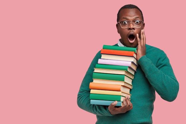 Młody uczeń afroamerykanów gospodarstwa stosu książek