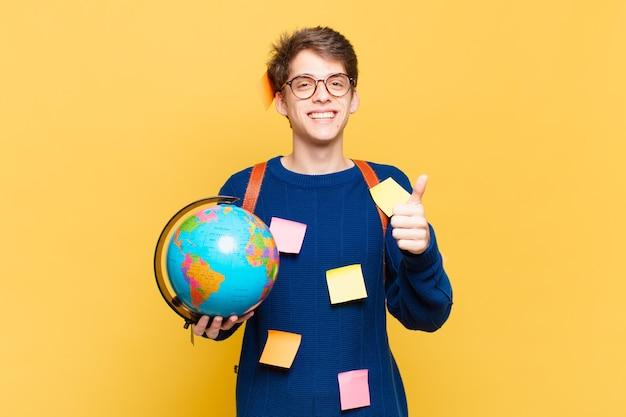 Młody uczeń chłopiec czuje się dumny, beztroski, pewny siebie i szczęśliwy, uśmiechając się pozytywnie z kciukami w górę