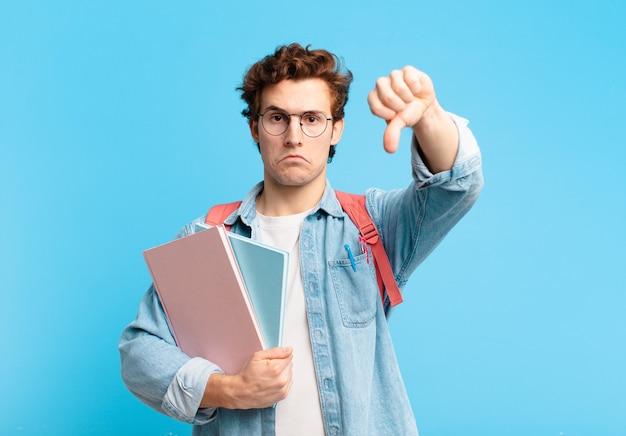 Młody uczeń chłopiec czuje się zły, zły, zirytowany, rozczarowany lub niezadowolony, pokazując kciuk w dół z poważnym spojrzeniem