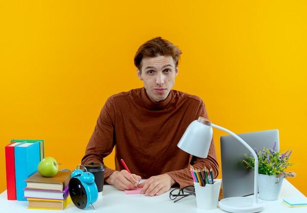 Młody uczeń chłopiec siedzi przy biurku z narzędzi szkolnych coś pisze