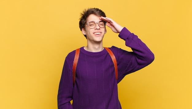 Młody uczeń chłopiec wygląda na szczęśliwego, zdziwionego i zdziwionego, uśmiechając się i uświadamiając sobie niesamowite i niewiarygodnie dobre wieści
