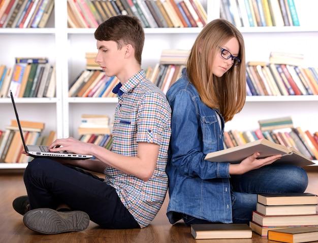 Młody uczeń czyta książkę i używa laptop.