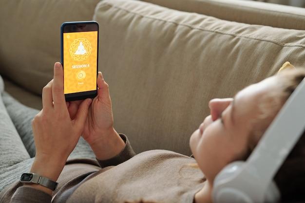 Młody uczeń kursu jogi online, leżąc na kanapie w domu i czekając na pobranie strony internetowej na ekranie smartfona