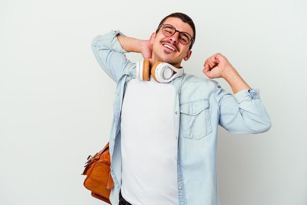 Młody uczeń mężczyzna słuchanie muzyki na białym tle na białej ścianie, rozciągając ramiona, zrelaksowana pozycja