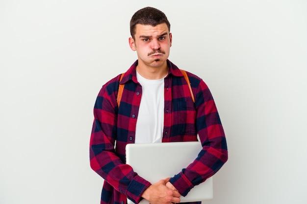 Młody uczeń mężczyzna trzyma laptopa na białym tle na białej ścianie wieje policzki, ma zmęczony wyraz