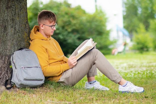 Młody uczeń mężczyzna w okularach czyta książkę, opierając się na drzewie w parku