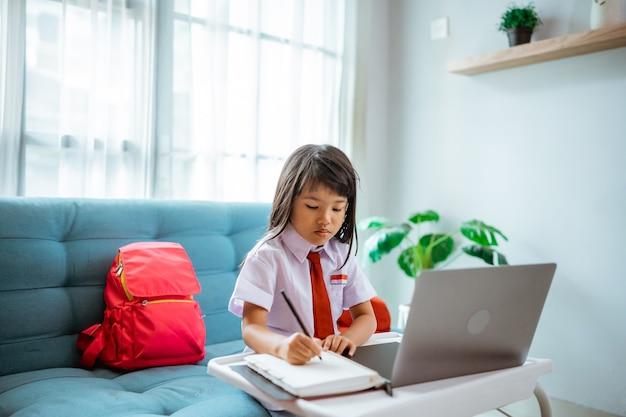 Młody uczeń pierwszej klasy w mundurku podczas nauki online z nauczycielem w domu