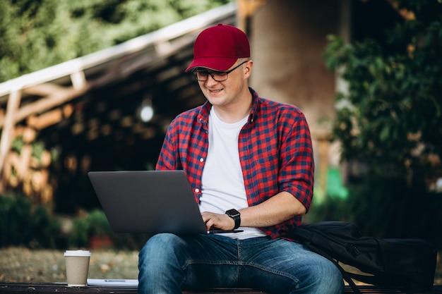 Młody uczeń pracuje na komputerze na zewnątrz kawiarni w parku