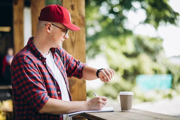 Młody uczeń pracuje w kawiarni w parku