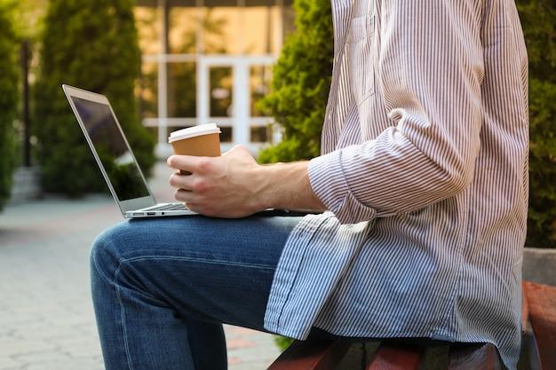 Młody uczeń pracuje w laptopie i pije kawę.