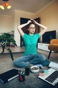 Młody uczeń przygotowuje się do lekcji online, siedząc na podłodze z laptopem i talerzem płatków śniadaniowych
