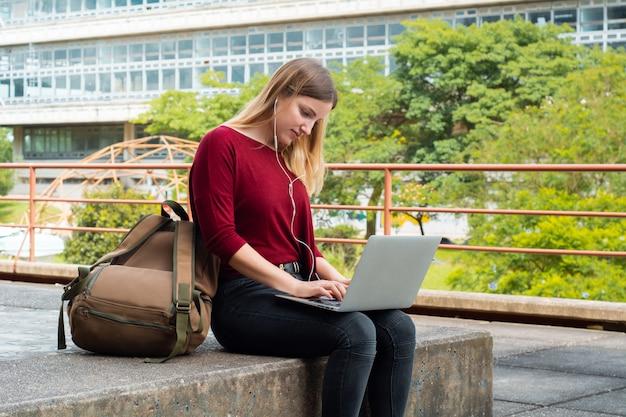 Młody uczeń używa laptop outdoors.