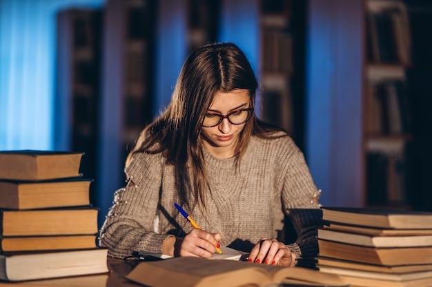 Młody uczeń w szkłach przygotowywa do egzaminu. dziewczyna wieczorem siedzi przy stole w bibliotece ze stosem książek