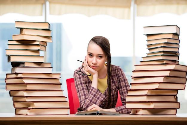 Młody uczeń z stertą książki