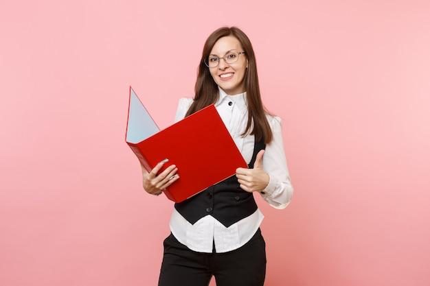 Młody udany biznes kobieta w okularach trzyma czerwoną teczkę na dokument dokumentów i pokazuje kciuk na białym tle na różowym tle. szefowa. osiągnięcie bogactwa kariery. skopiuj miejsce na reklamę.