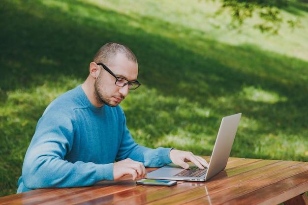 Młody udany inteligentny człowiek biznesmen lub student w okularach dorywczo niebieska koszula siedzi przy stole z telefonem komórkowym w parku miejskim przy użyciu laptopa pracującego na świeżym powietrzu na zielonym tle. koncepcja mobilnego biura.
