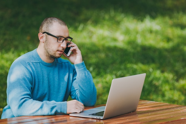 Młody udany uśmiechnięty inteligentny człowiek biznesmen lub student w dorywczo niebieska koszula, okulary siedzi przy stole, rozmawia przez telefon komórkowy w parku miejskim za pomocą laptopa, pracując na zewnątrz. koncepcja mobilnego biura.