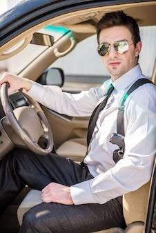 Młody ufny biznesmen w okularach przeciwsłonecznych z pistoletem.