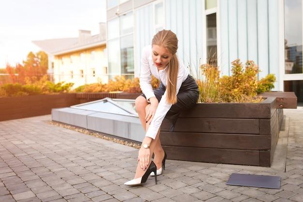 Młody urzędnik trzyma stopę z noszenia butów na wysokim obcasie. zmęczone nogi młodej kobiety biznesu po męczącym dniu