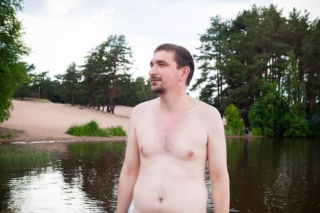 Młody uśmiechający się nagi mężczyzna stojący w jeziorze na tle zalesionych brzegów.