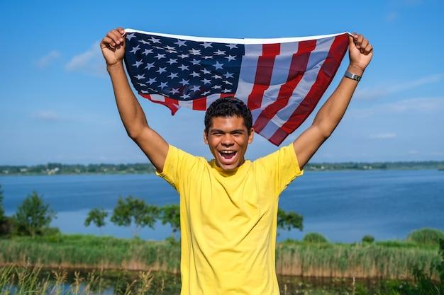 Młody uśmiechnięty afroamerykanin patrząc na kamerę i dumnie trzymający macha amerykańską flagę w wyciągniętych ramionach na tle błękitnego nieba latem