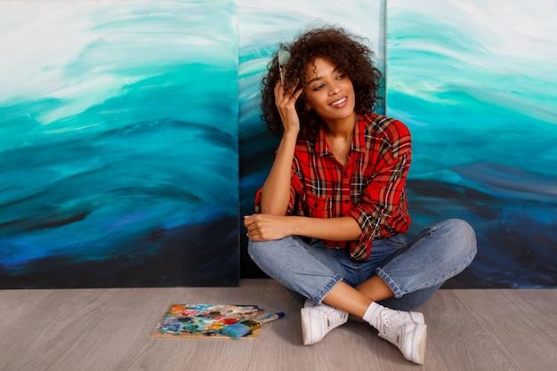 Młody uśmiechnięty artysta czarny kobieta w studio trzyma pędzel. inspirowana studentka siedząca nad jej dziełami.