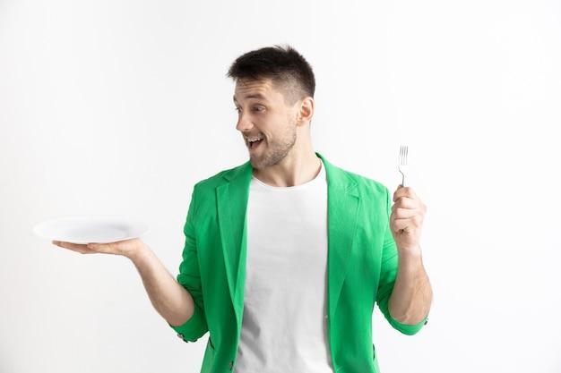 Młody uśmiechnięty atrakcyjny kaukaski facet trzyma puste naczynie i widelec na białym tle na szarej przestrzeni. skopiuj miejsce i mock up