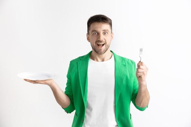 Młody uśmiechnięty atrakcyjny kaukaski facet trzyma puste naczynie i widelec na białym tle na szarym tle. skopiuj miejsce i mock up. puste tło szablonu.