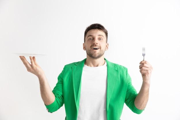 Młody uśmiechnięty atrakcyjny kaukaski facet trzyma puste naczynie i widelec na szarym tle.